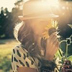 femme au chapeau sentant un tournesol