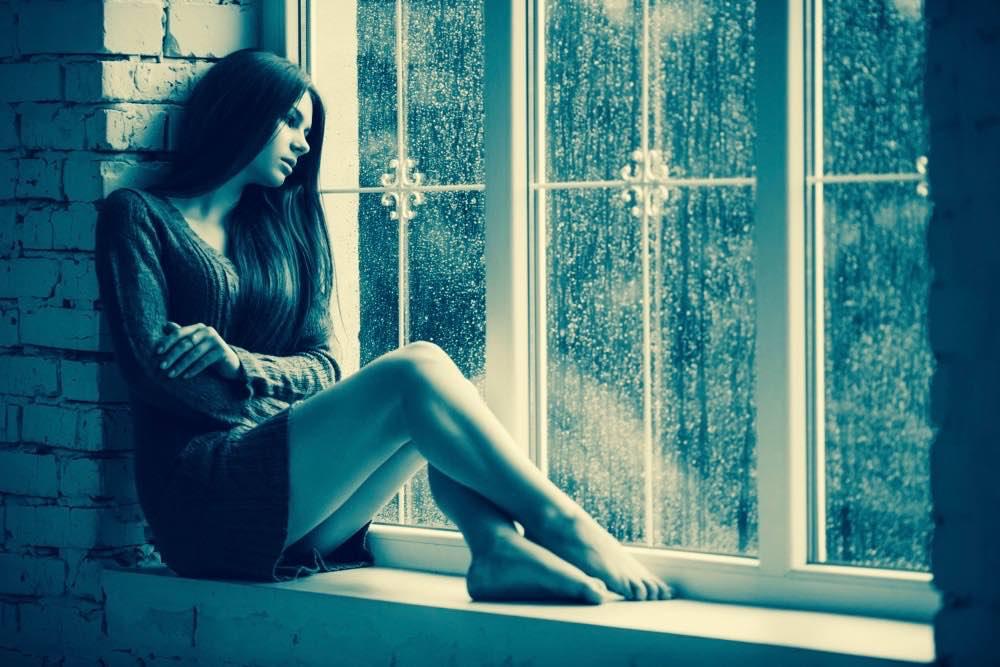 femme seule a la fenetre pluie